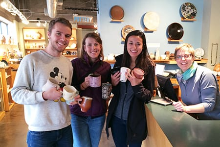 Liam Hannan '18, Studio Art Technician and Visiting Assistant Professor of Art and Art History Kate Fisher '00, and Emily Tani-Winegarden '16 pick up cups at the Northern Clay Center in Minneapolis.
