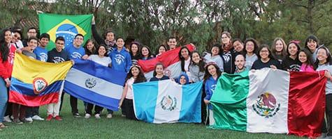 Participants and facilitators at Empoderando a Latinoamerica 2016 pose with flags from their countries of origin.