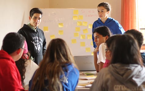 St. Olaf College student Pedro Monque stands in front of a classroom to facilitate a peace agency workshop that he and several other St. Olaf students developed.