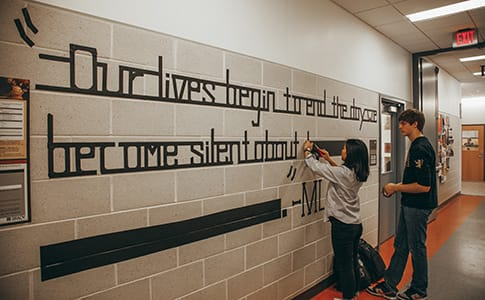 Students create a large-scale tape drawing of a Martin Luther King Jr. quote.