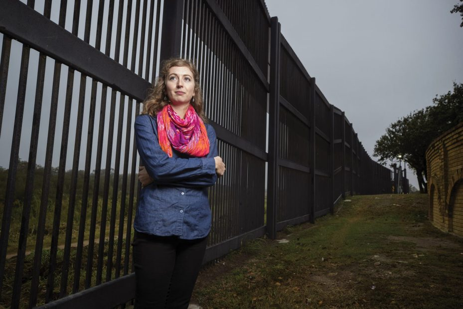 Woman standing in front of fence.