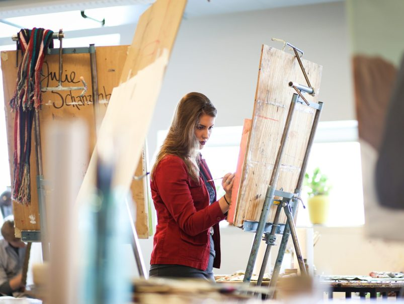 Woman in red jacket painting on a canvas.
