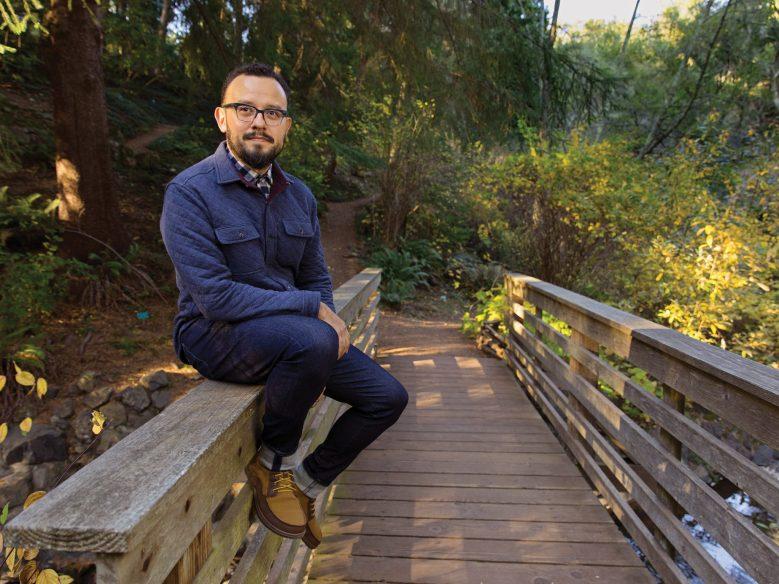 Man in blue jacket sitting on left railing of bridge.
