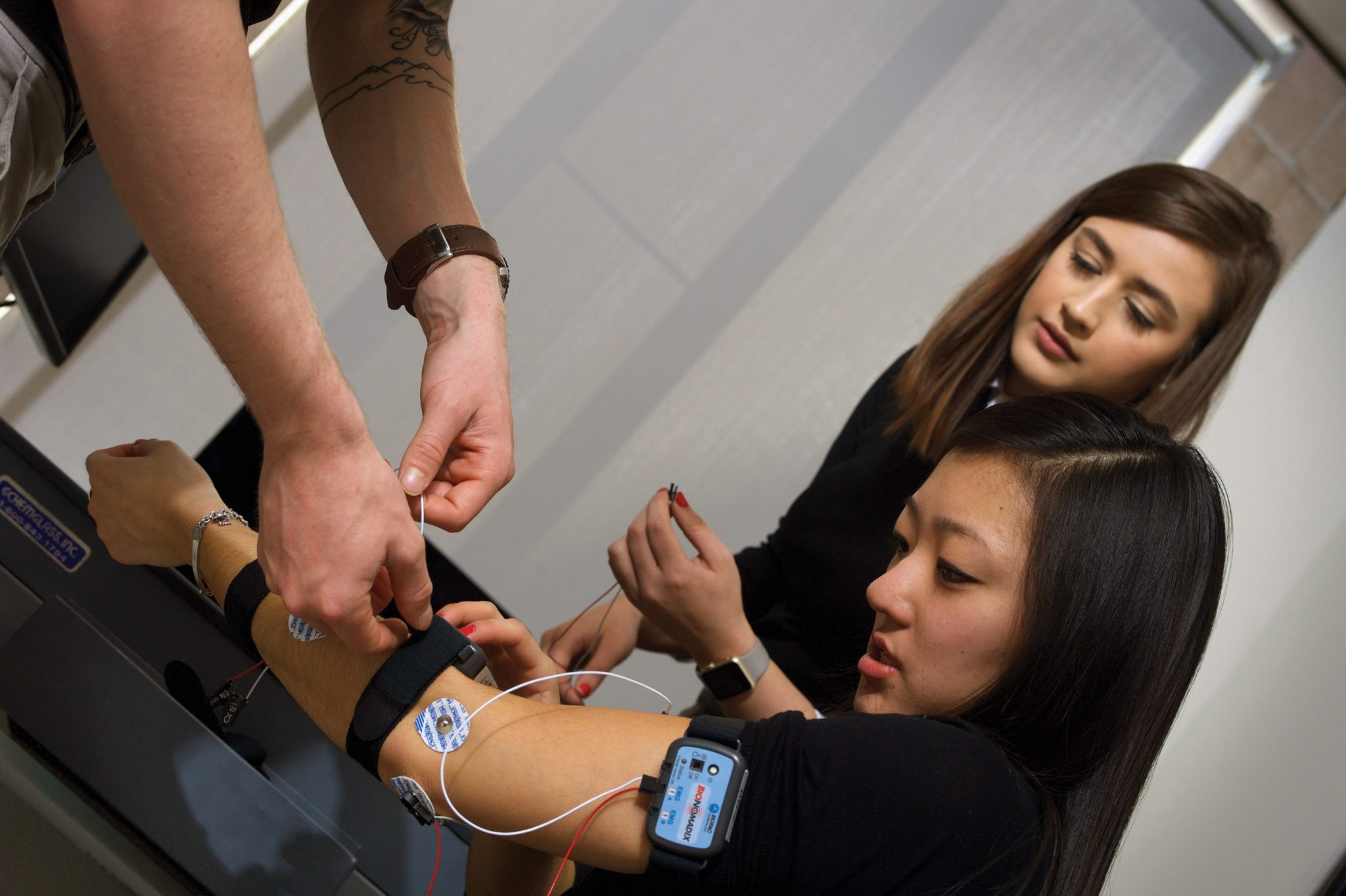 Student places EMG sensors on another student