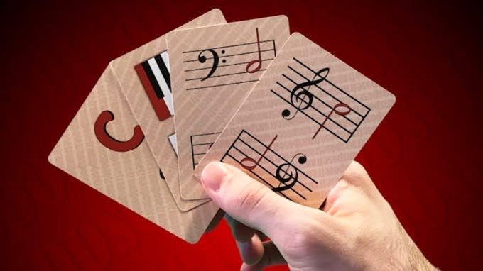 A hand holds four cards from the Transpose game in front of a red background.