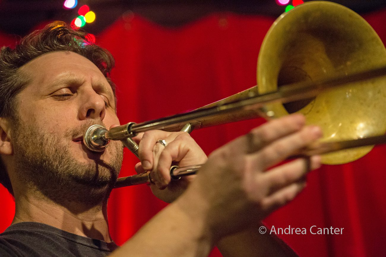 St. Olaf jazz professor and conductor JC Sanford plays trombone in front of a red curtain.