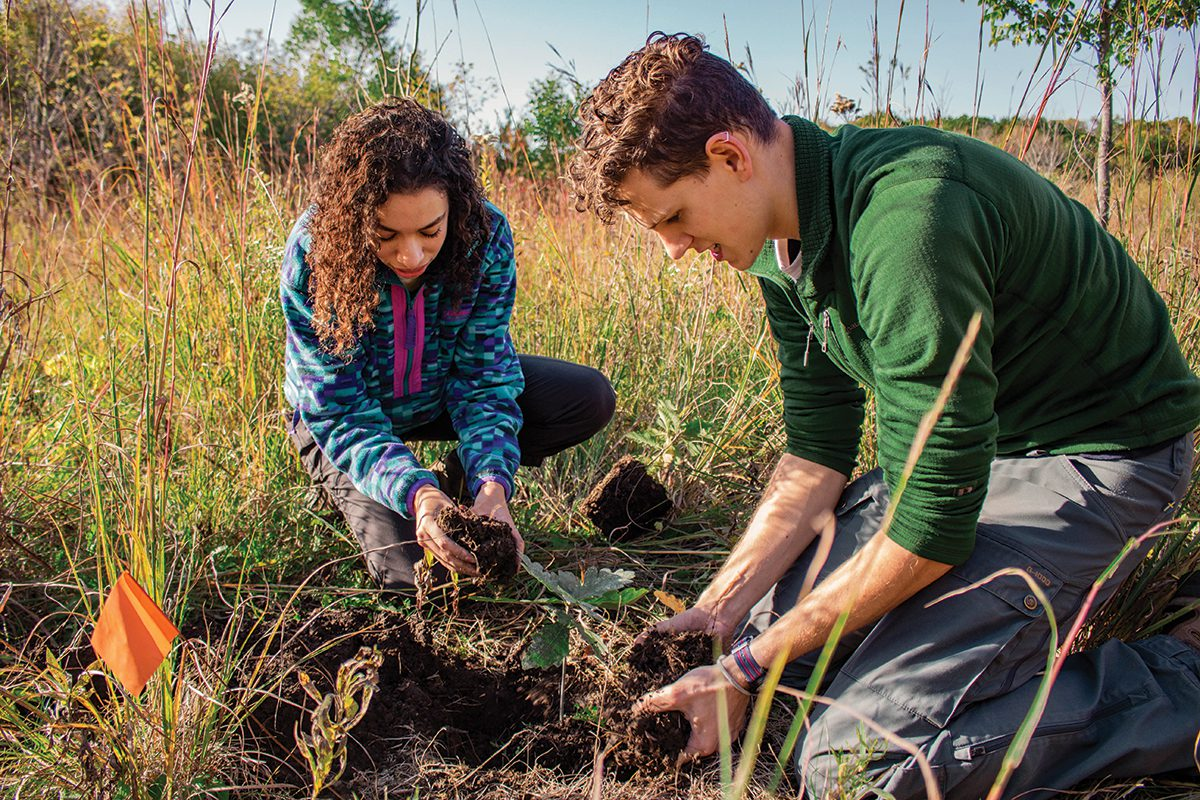 Student naturalists Izzy Istephanous and Henry Henson plant trees in the Natural Lands.