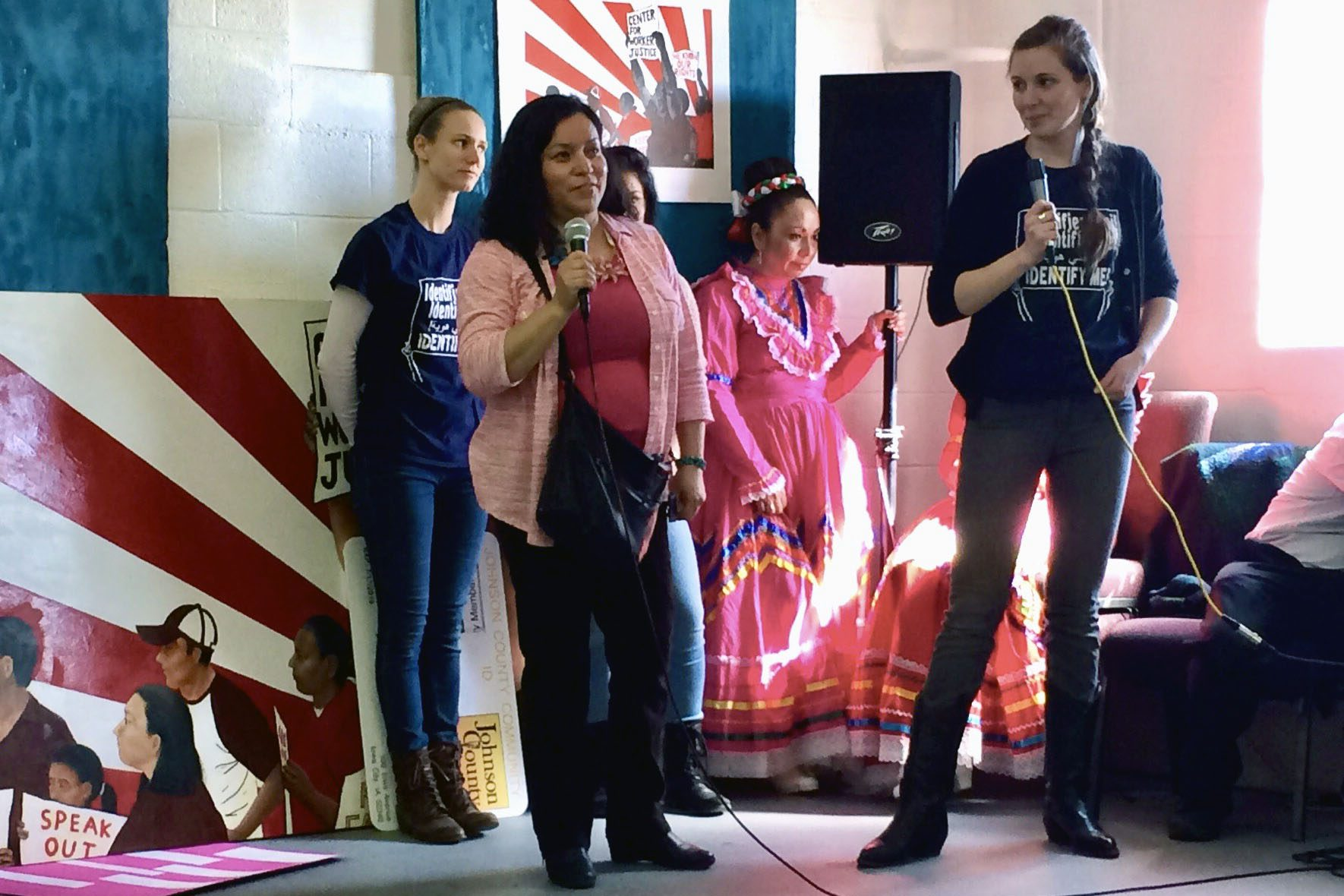 Nicole Novak (right) and a leader from the Center for Worker Justice of Eastern Iowa speak on a stage with microphones in front of three other women and protest art.