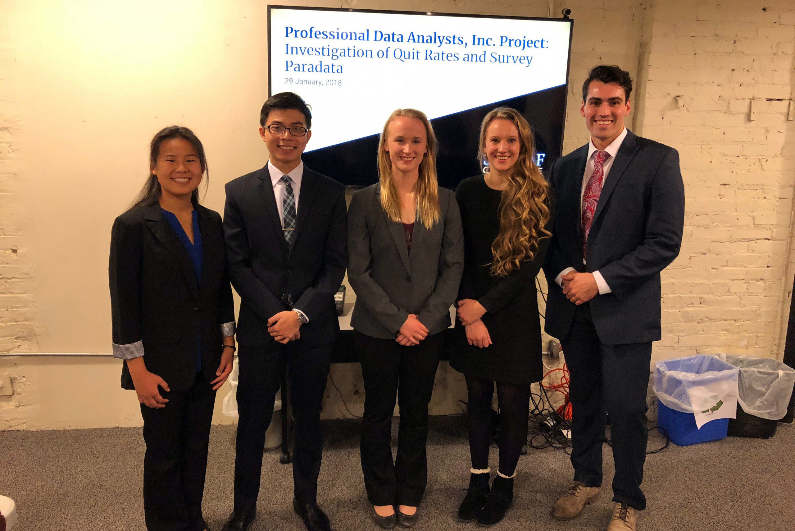 Portrait of (left to right) Leah Andrews, Cuong Quoc Nguyen, Rose Peterson, Kalley Johnson, and Quinton Neville in front of a television screen with their MSCS Practicum presentation.