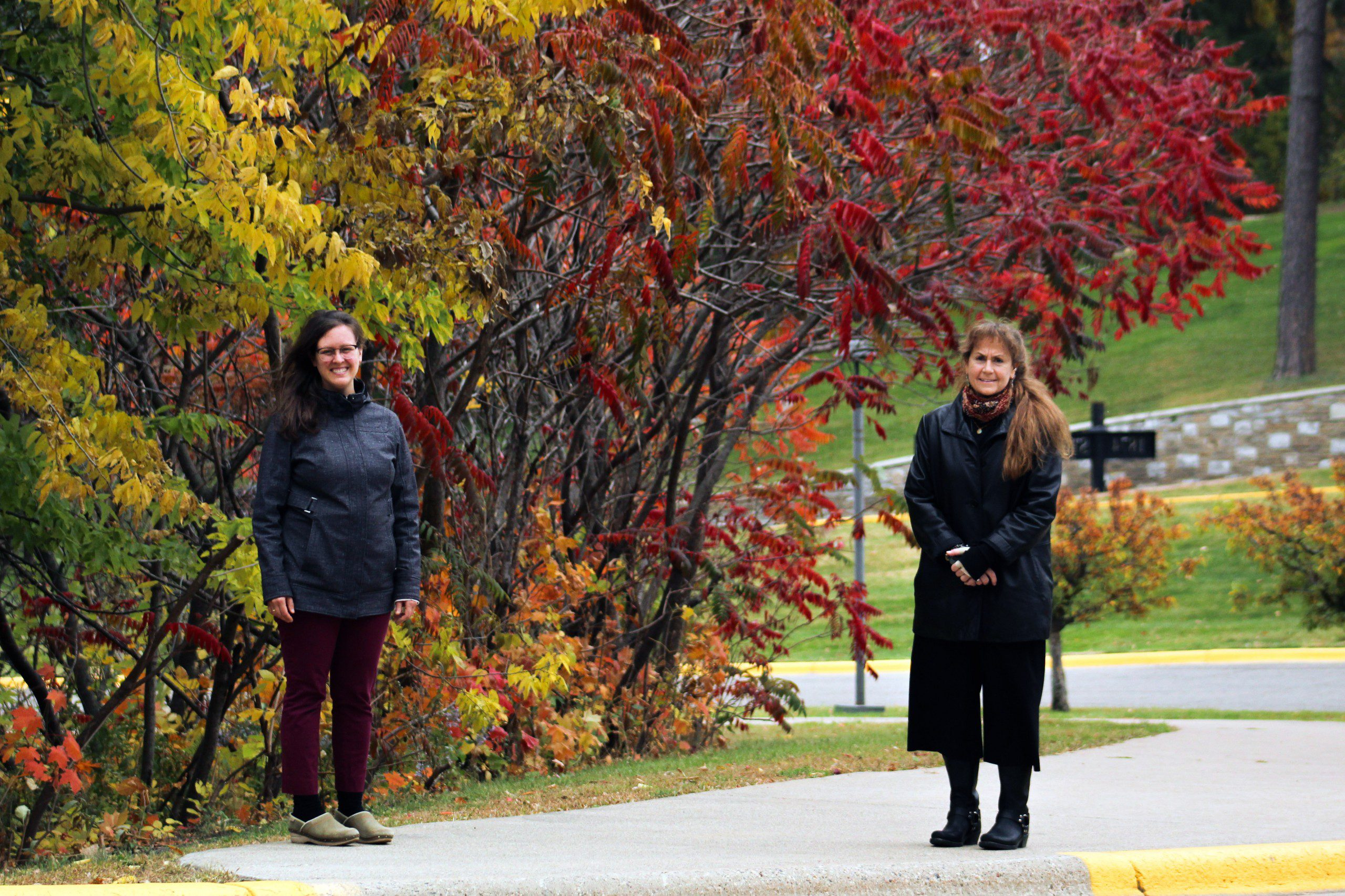 Portrait of Bridget Draxler (left) and Diane LeBlanc outside with trees in the background.