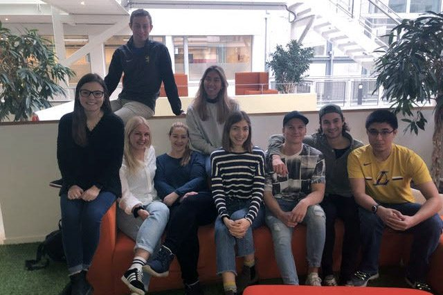 Group of Norway Innovation Scholars sit on a couch with a white building in the background.