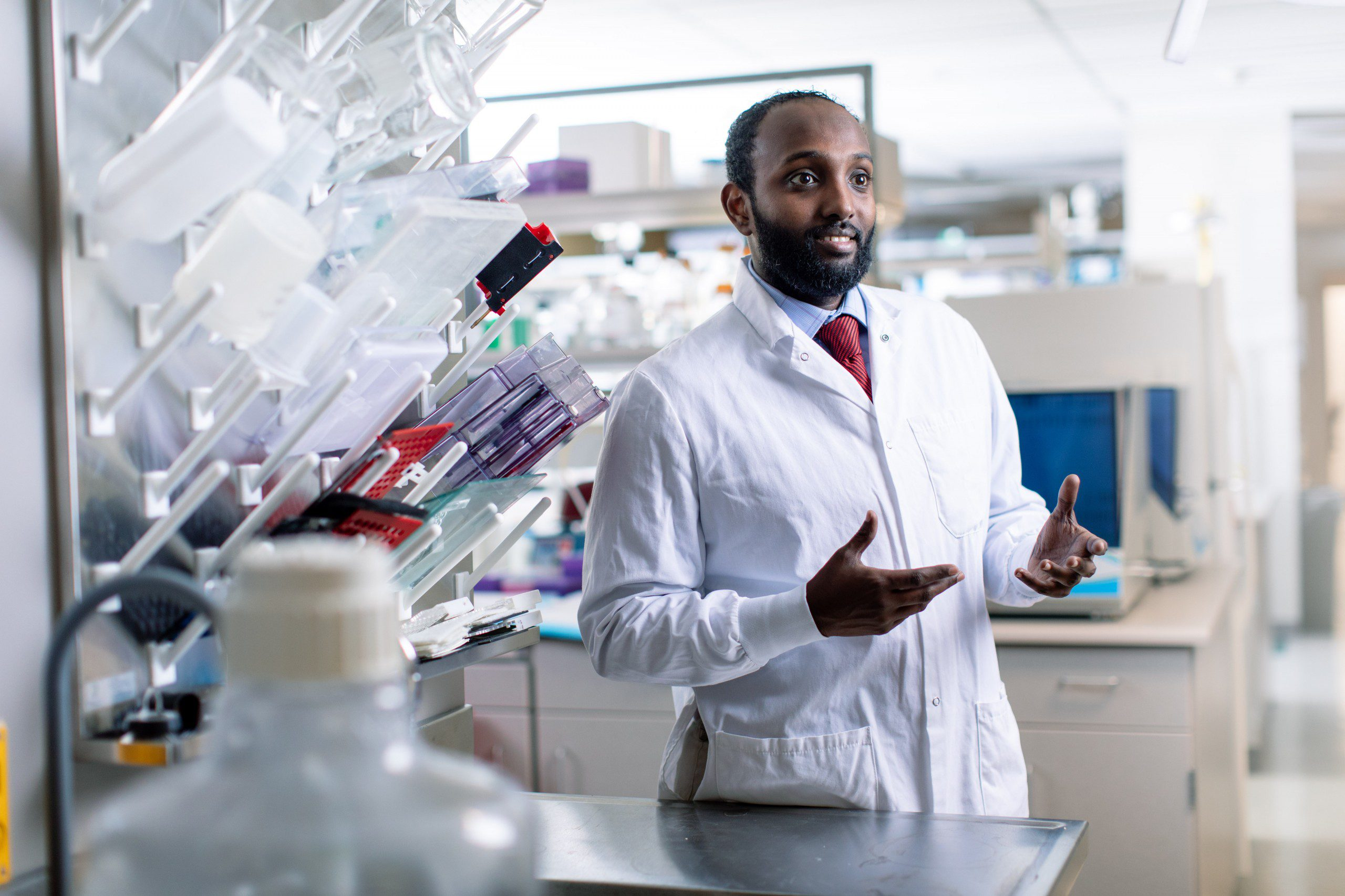 Portrait of Essa Mohamed wearing a lab coat in a laboratory.