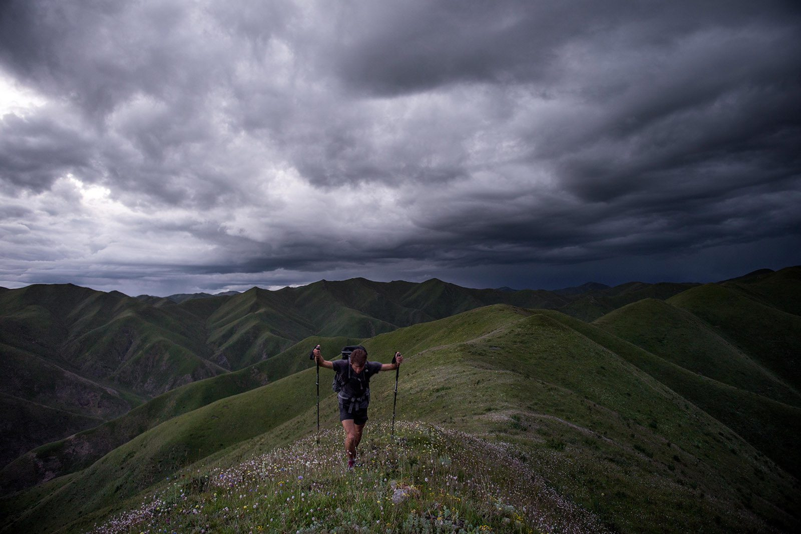Kyle Obermann hikes on a mountain with mountains and dark clouds in the background.
