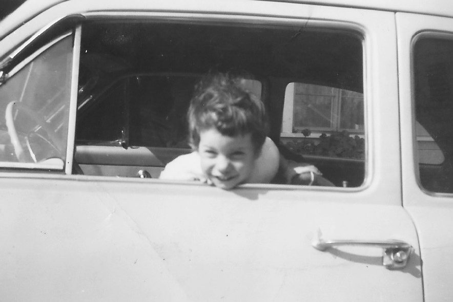 Professor of History Judy Kutulas as a child, in a black-and-white photo, leaning out of a car window.