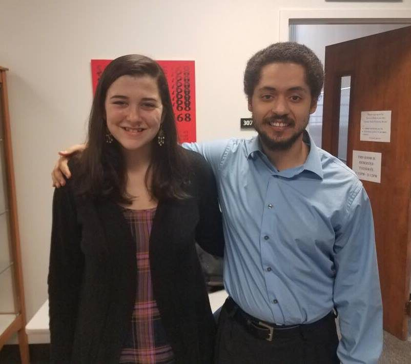 Portrait of Emily Hynes (left) and Aaron Harcus (right) with an open door in the background.