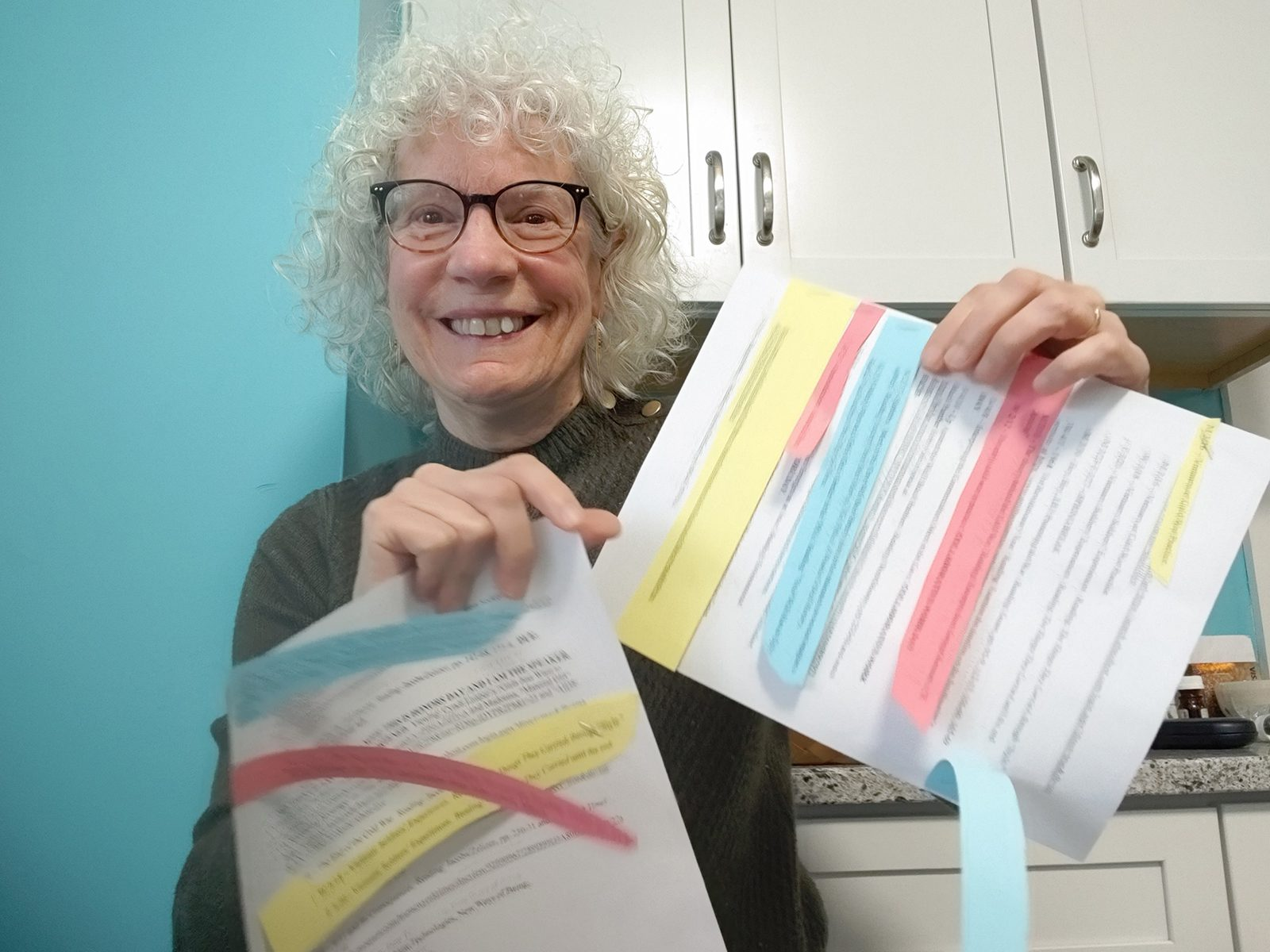 Professor of History Judy Kutulas holds a paper with multicolored additions and corrections stapled to the pages.