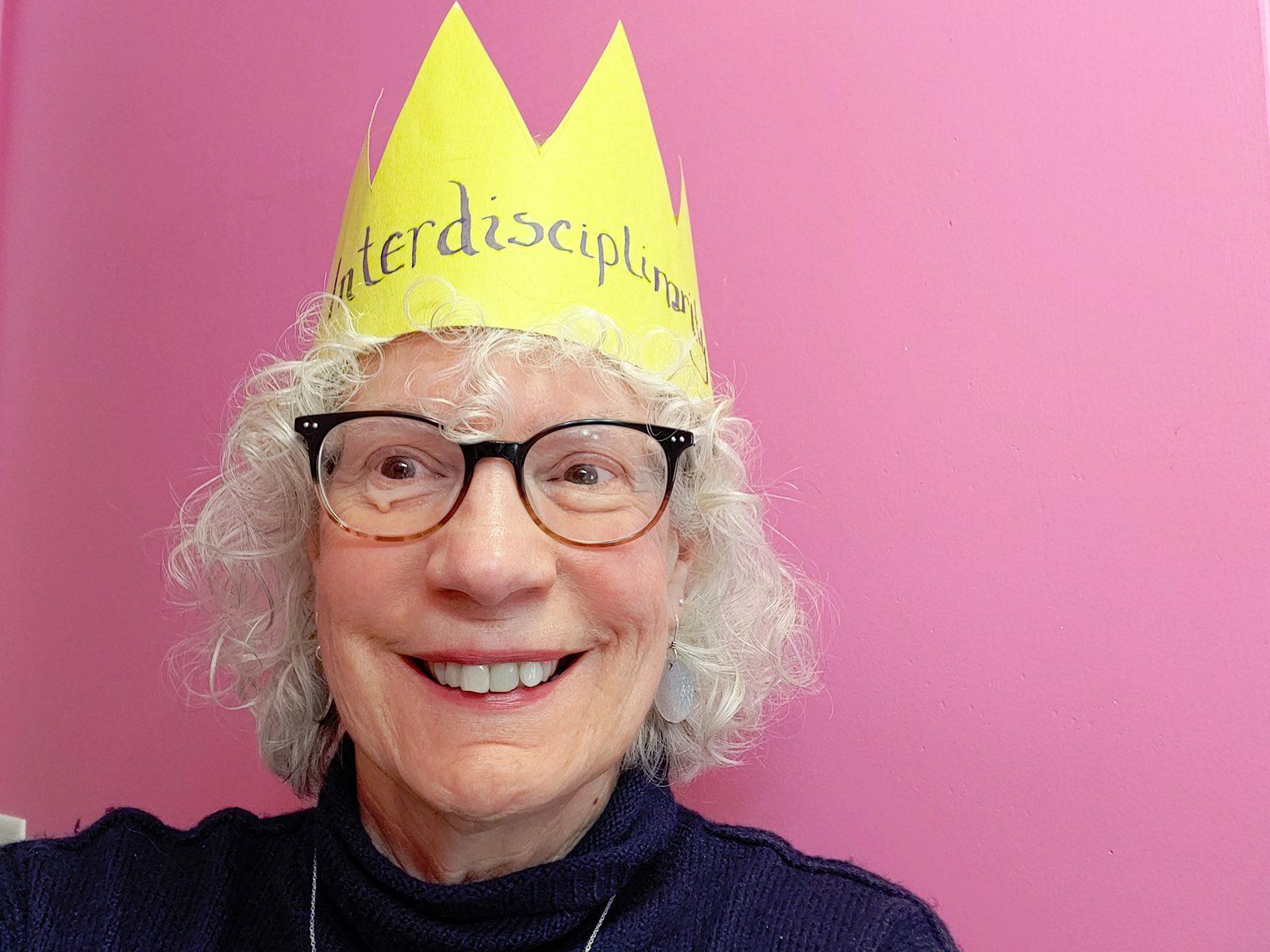 "Portrait of Professor of History Judy Kutulas wearing a gold paper crown with ""interdisciplinary studies"" written on it."