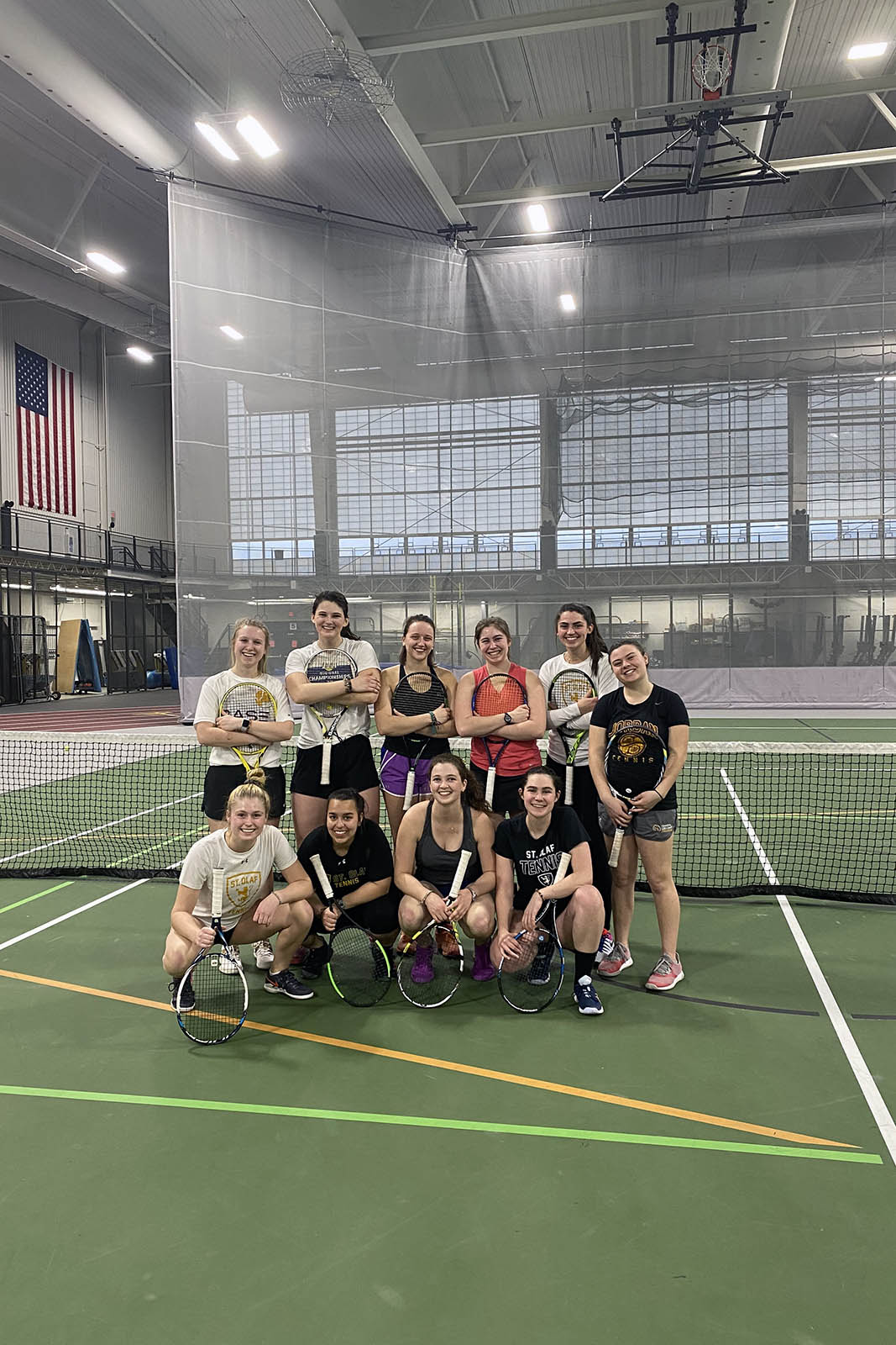 Picture of members of the St. Olaf women's tennis team holding rackets in the indoor tennis court in Tostrud.