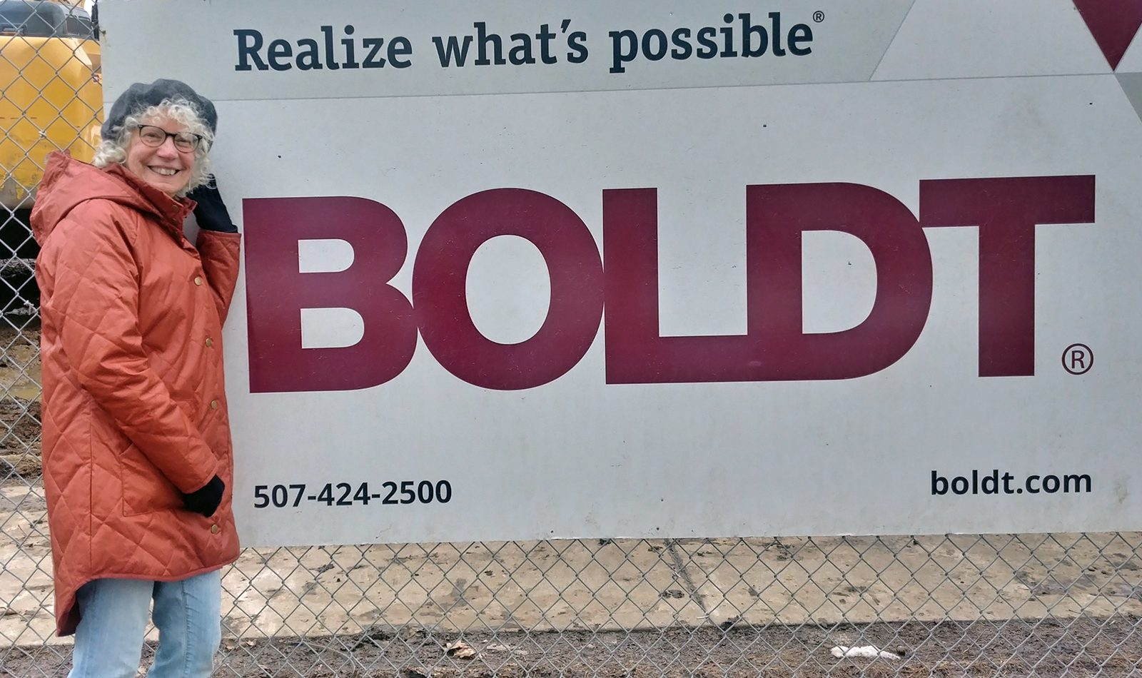 """Professor of History Judy Kutulas in front of a Boldt Construction sign on campus that captures the key message she took away from the COVID-19 pandemic: """"Realize what's possible."""""""