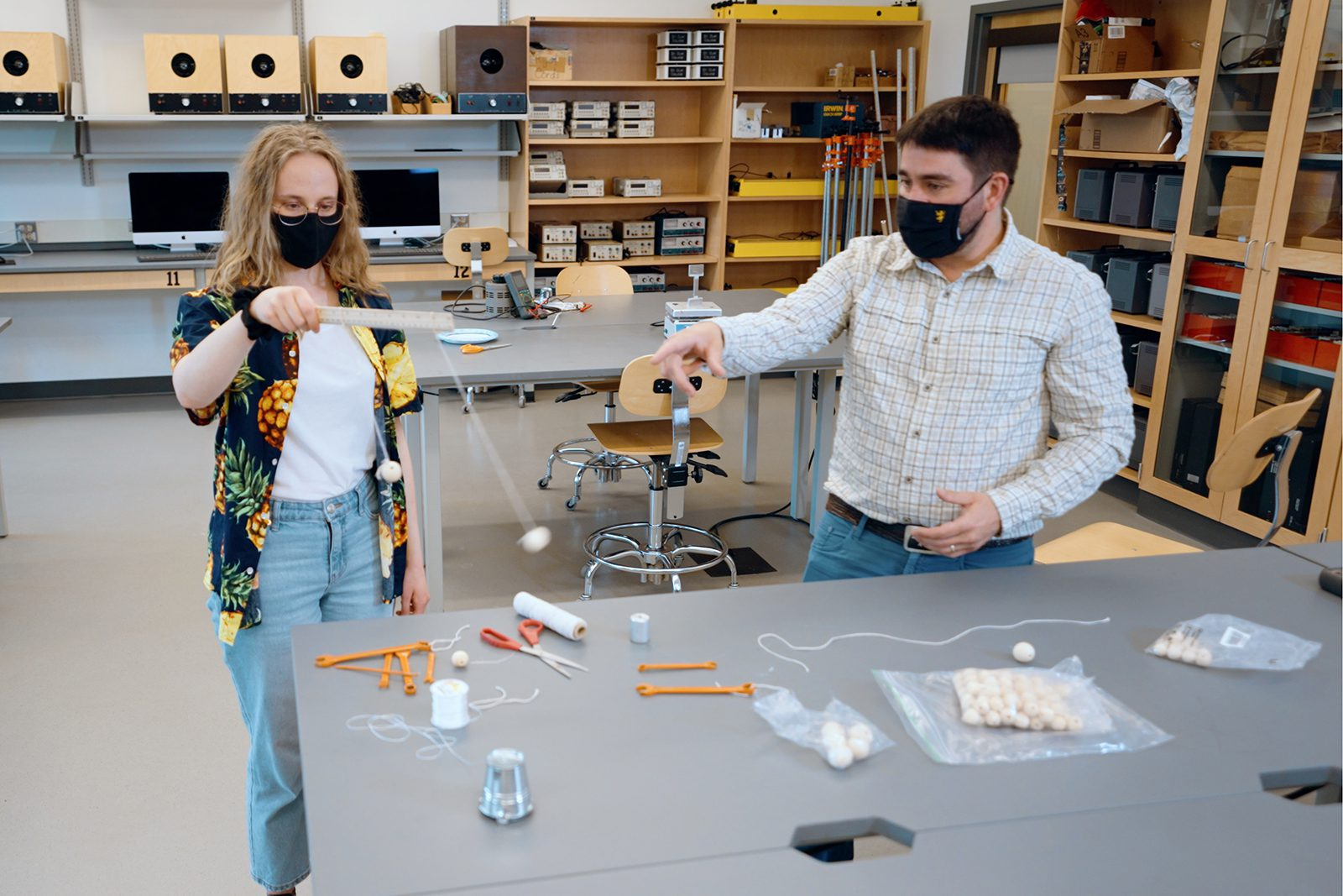 Elizabeth Leeser '23 (left) tests one of the science kits with the guidance of physics faculty member Eric Hazlett.