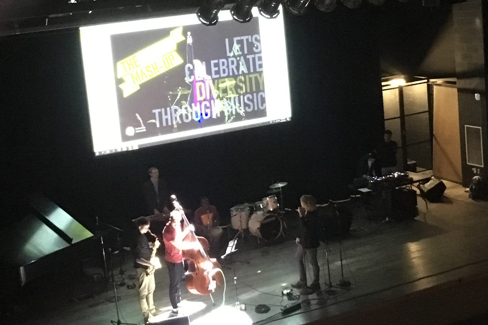"Photo of student musicians on a stage with a screen that reads ""Let's Celebrate Diversity Through Music!"" behind them."