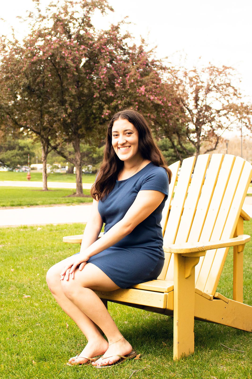 Portrait of Allyvia Garza on a yellow adirondack chair with trees in the background.