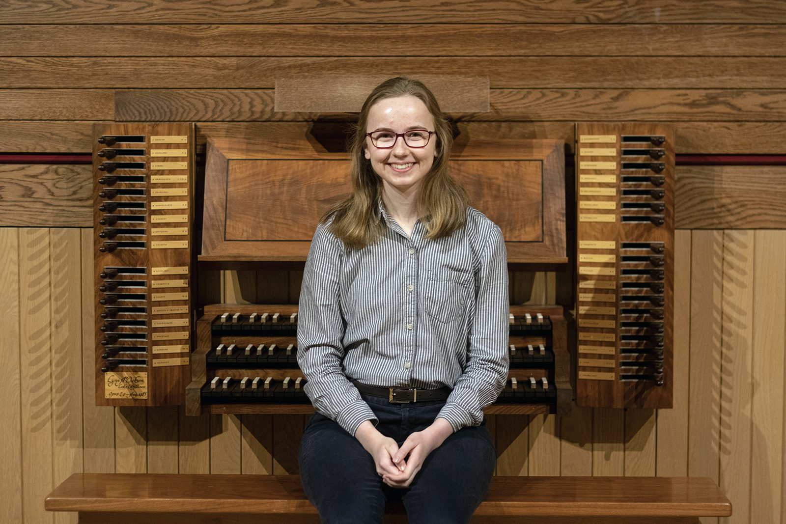 Portrait of Katie Gunn in front of an organ.