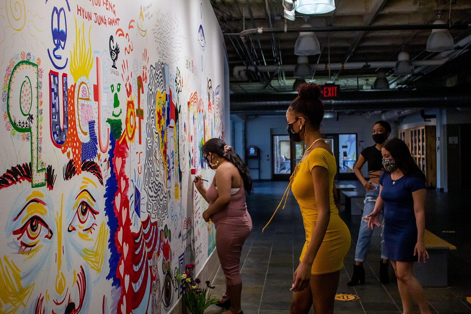 From left to right, Joanna Perez, Tija Atkins, Sophia Evans, and Allyvia Garza gather around a wall mural with double doors in the background.