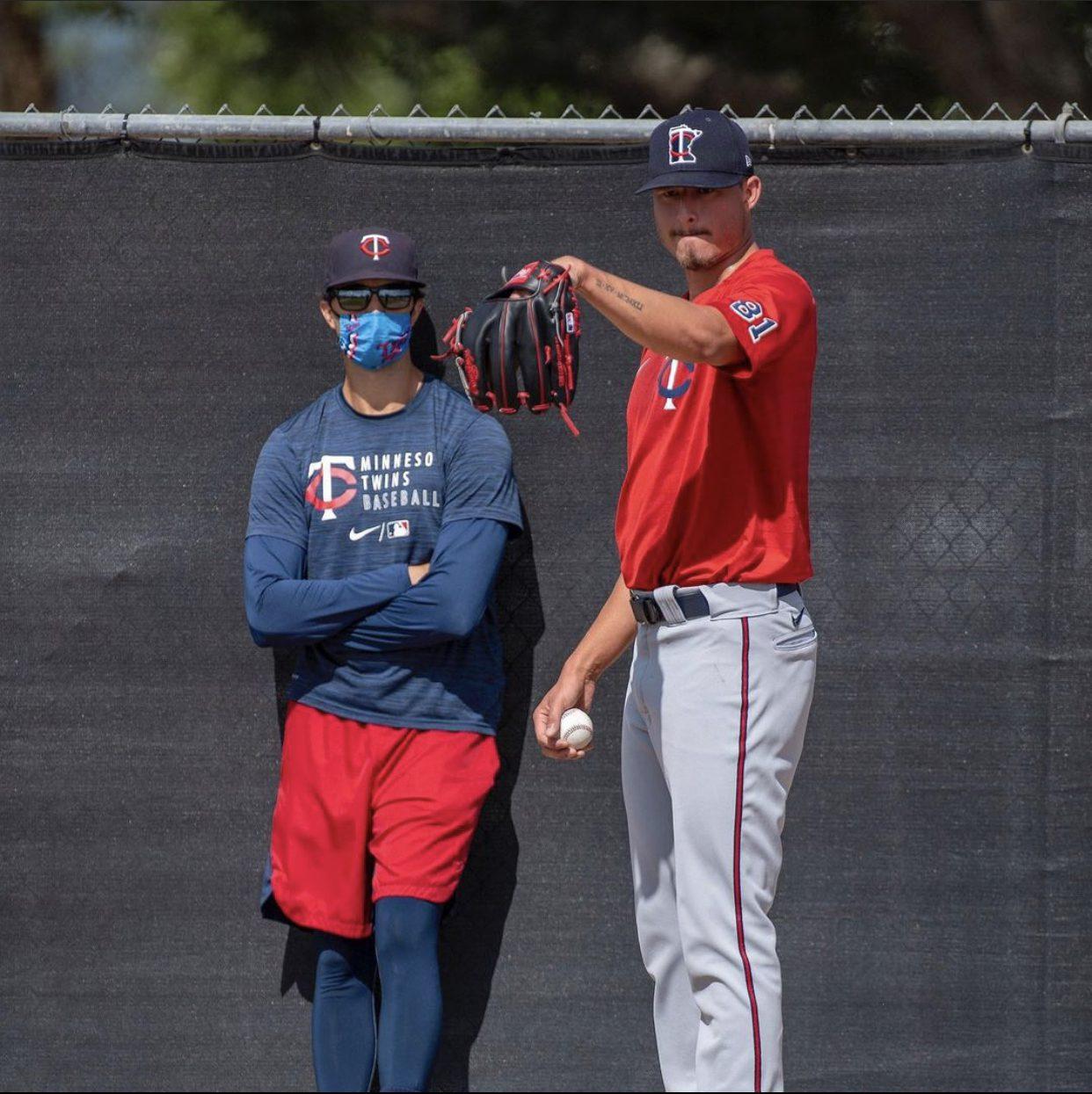 Anders Dzurak '13 (left) works with pitcher Jordan Balazovic this spring.