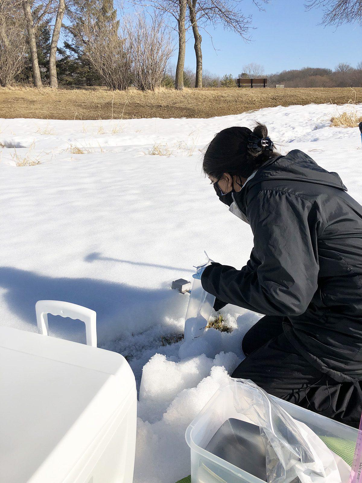 Kavya Devgun '21 collects snow samples for research behind Skoglund Athletic Center.