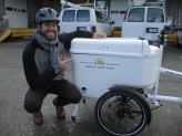 Man in 20s or 30s poses against bike with container in front displaying SAF logo