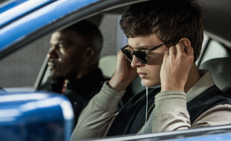 Baby (ANSEL ELGORT) and Bats (JAMIE FOXX) on the way to the post office job with Buddy (JON HAMM) and Darling (EIZA GONZALEZ) as cops pull up next to them in TriStar Pictures' BABY DRIVER.