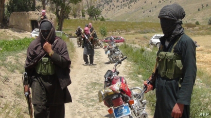 FILE - Taliban fighters stand with their weapons in Ahmad Aba district, on the outskirts of Gardez, the capital of Paktia province, Afghanistan, July 18, 2017.