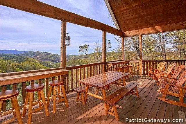 Covered deck with a picnic table and bar table at Privacy & A View, a rental cabin in Pigeon Forge, TN