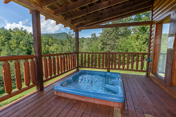 A hot tub on a covered porch overlooking the Smoky Mountains