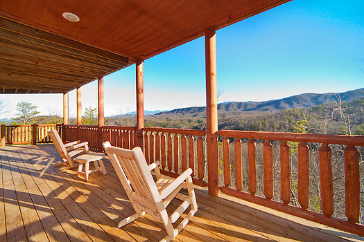 rocking chairs on a porch overlooking a mountain