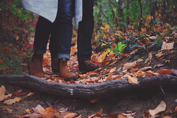 a man and a woman walking on a leaf-covered trail