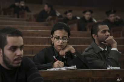 FILE - Mahinour el-Masry, an Egyptian activist, takes notes during a trial session of activists facing charges on organizing unauthorized protests, at a courtroom in Cairo, Egypt, Dec. 4, 2014..