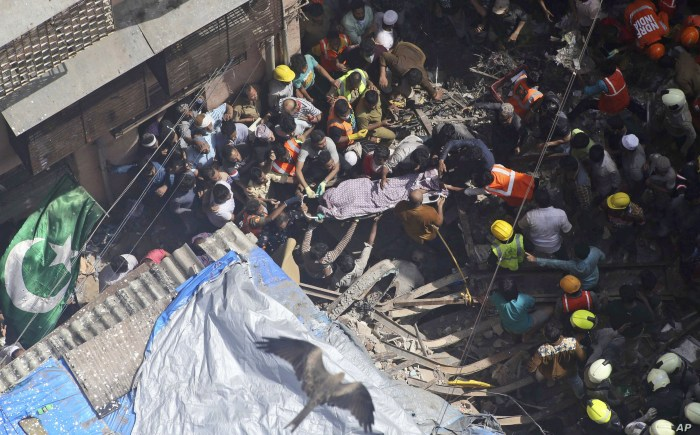 Rescuers carry the body of a victim at the site of a building that collapsed in Mumbai, India, Tuesday, July 16, 2019. A four-story residential building collapsed Tuesday in a crowded neighborhood in Mumbai, India's financial and entertainment…