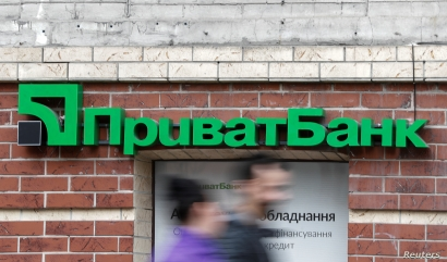 FILE - People walk past a branch of PrivatBank, the country's biggest lender, in Kyiv, Ukraine, April 18, 2019.