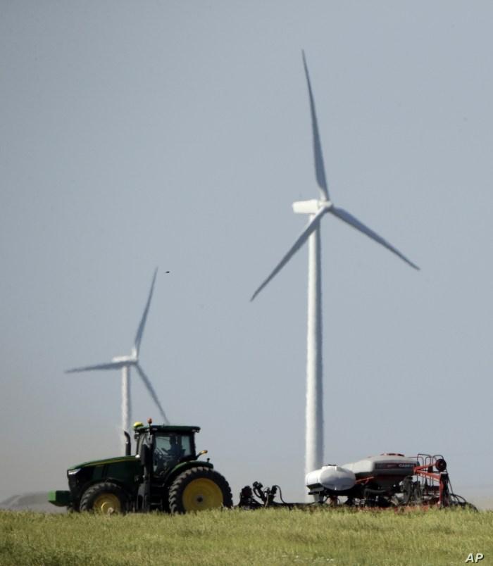 A farmer plants corn against a backdrop of wind turbines Saturday, June 8, 2019, in a field near Vesper, Kan. (AP Photo/Charlie Riedel)