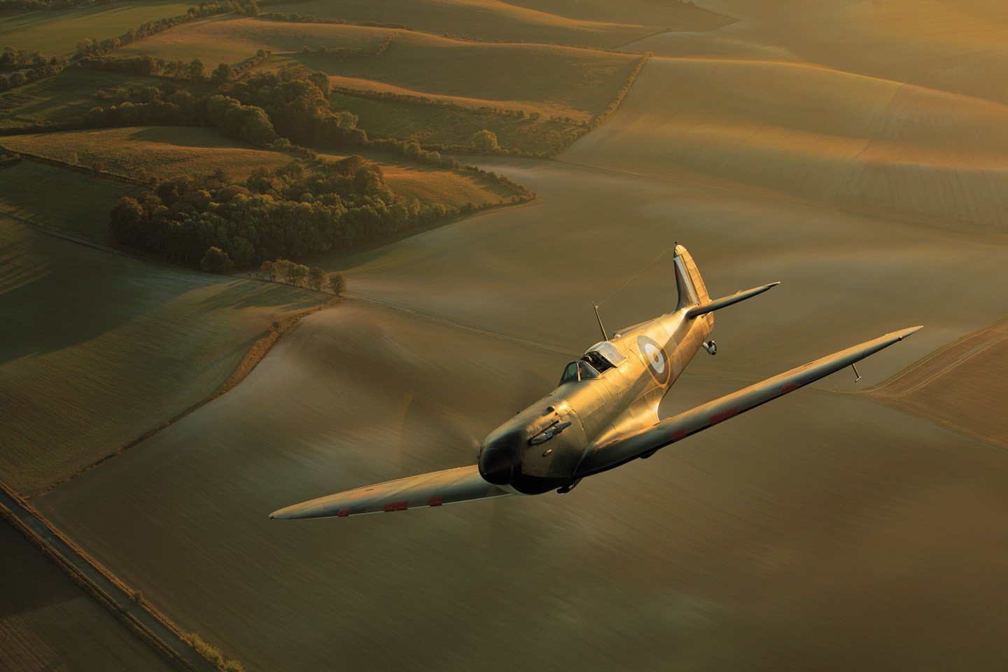 A Spitfire flying above British fields for RAFBF Storylines