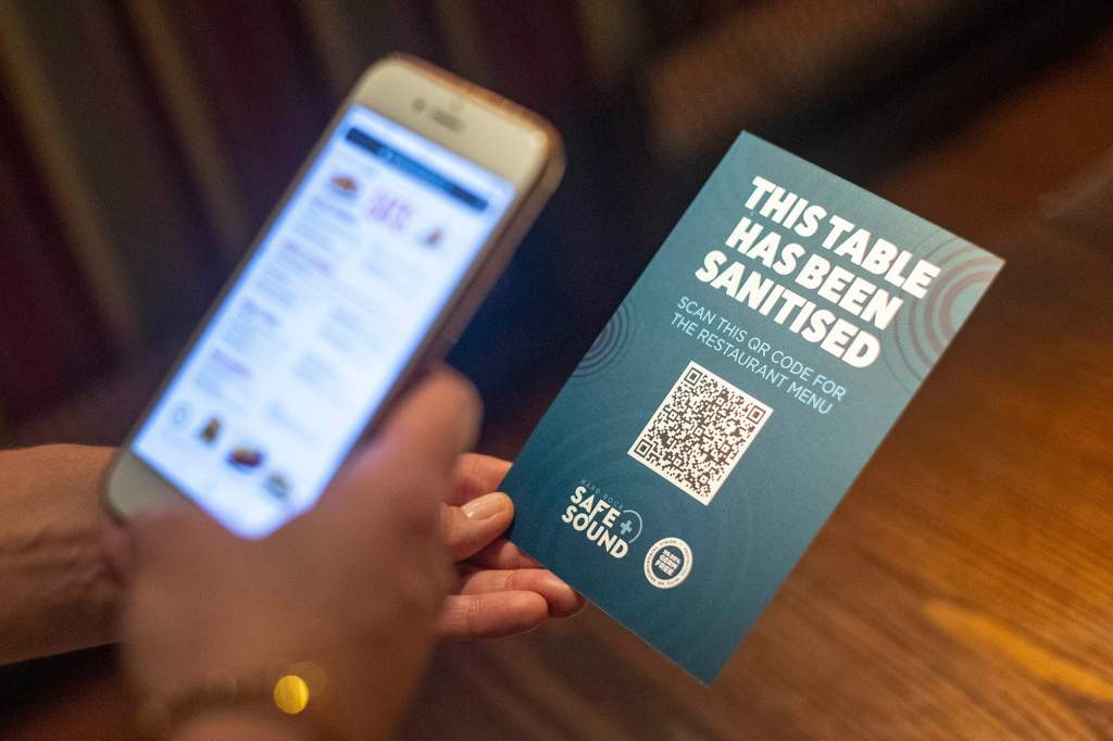A menu card with a QR code being scanned by a mobile phone