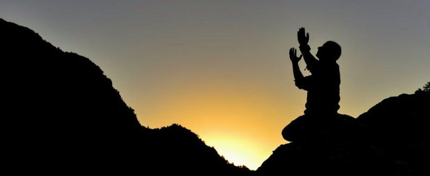 man praying on mountain