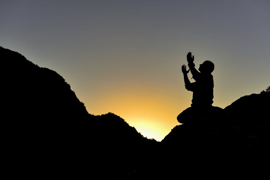 man praying on mountain