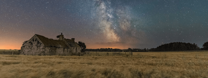 Cabin in a field on a starry night