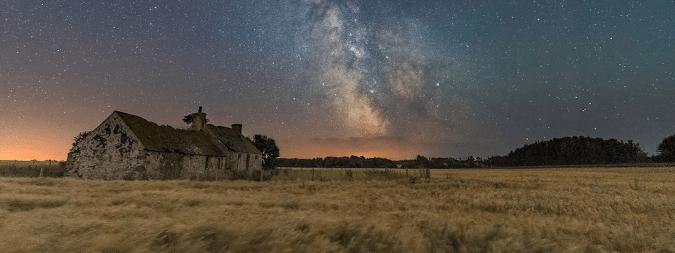 Cabin in a field on a starry night