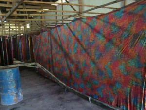 Wraps are hung in the open air, protected by a ceiling, for inspection.