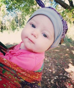 Annie leans away from her mother. She is wrapped in a Jennifer Wrapsody Hybrid and wearing a purple beanie in the Aphrodite colorway. She looks directly at the camera, smirking, a spot of drool on her chin.