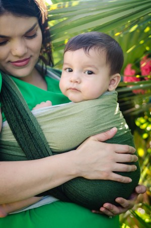 Image of a latinx woman looking down at her baby worn in a dark green to light green grad dyed wrap.